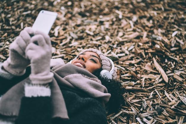 冬の間にマドリードの王宮の近くの木の平和に横たわっている携帯電話の若い黒人女性