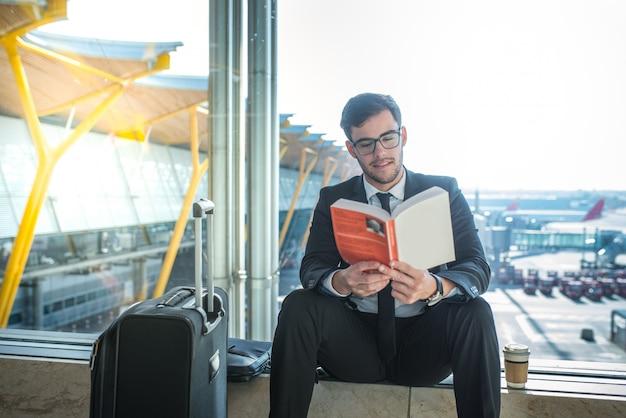 Красивый бизнесмен читает книгу в аэропорту, сидя рядом с окном
