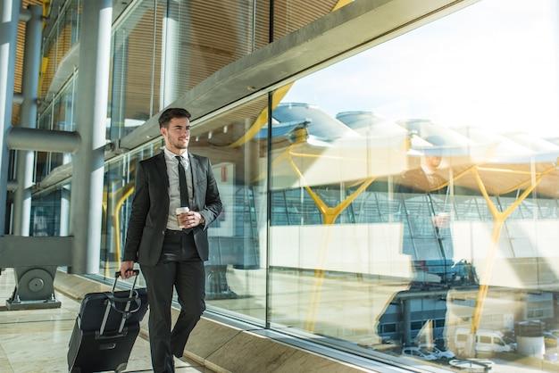 Молодой предприниматель, ходить в аэропорту с багажом, улыбаясь с кофе