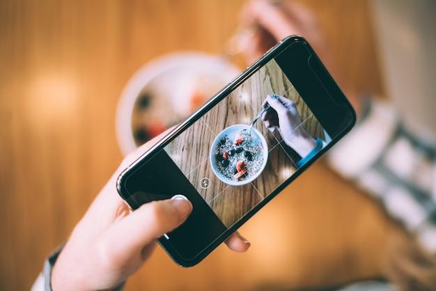 ボウル朝食オート麦とフルーツの写真を撮る女性