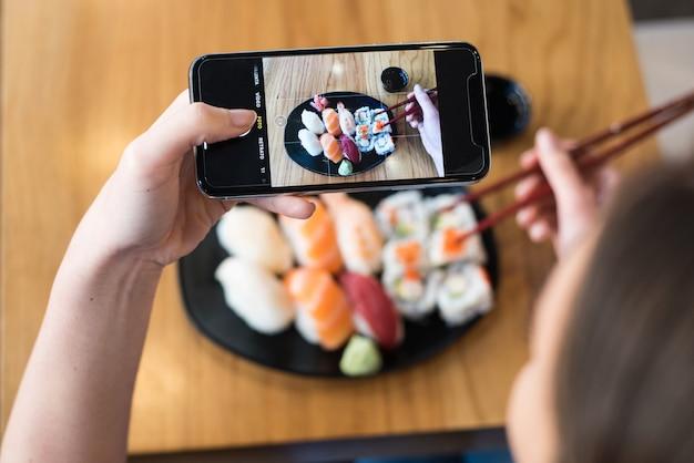 テーブルの上に寿司の写真を撮る女性のトップビュー