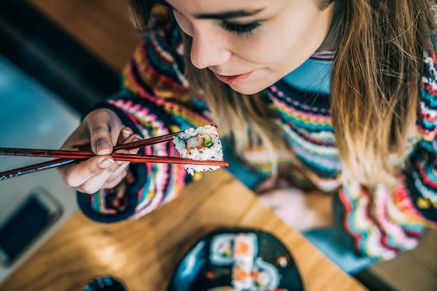 上から寿司を食べる女