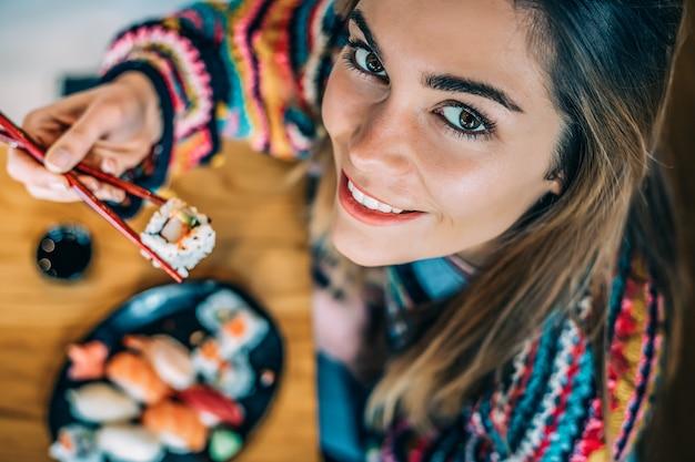 Сверху посевная женщина ест суши