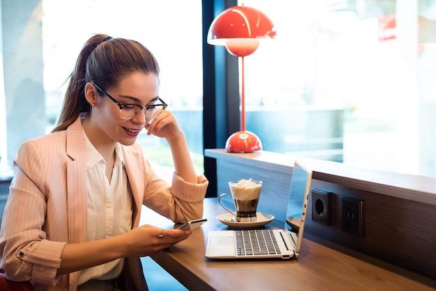 ノートパソコン、スマートフォン、レストランでコーヒーを持つ若い美しい女性