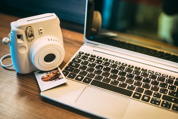 Мгновенная камера и фотографии с ноутбуком на столе