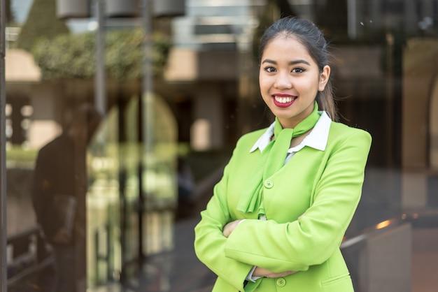 Молодая женщина шорт или команда, улыбаясь скрещенными руками зеленый