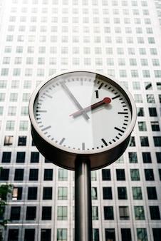 背景に背の高い建物が付いている通りの時計