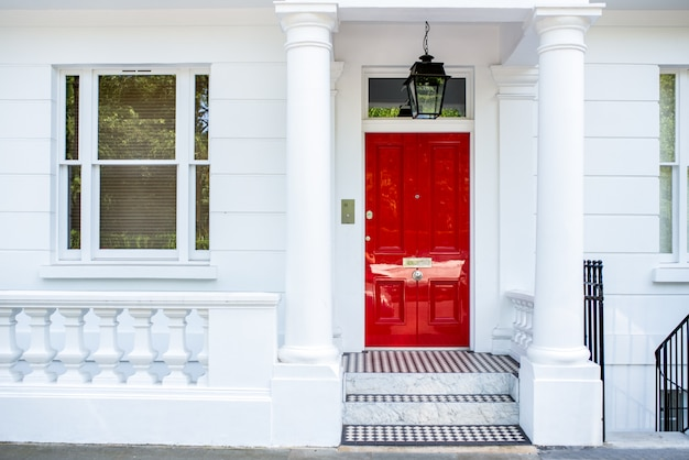 ノッティングヒルの白い家の正面の美しい赤いドア
