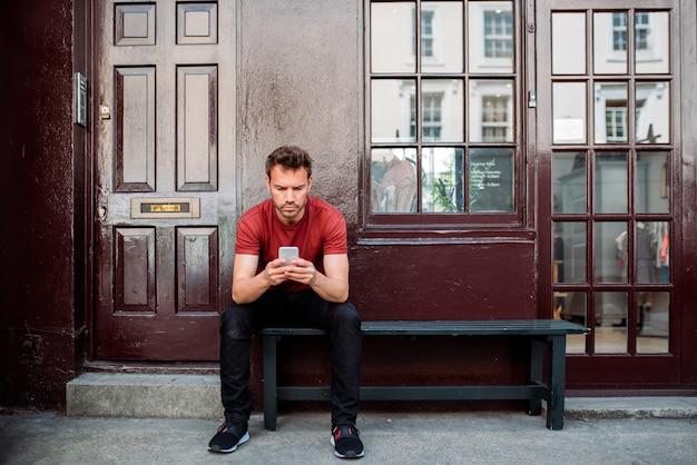 美しい栗色の背景のベンチに座っている男