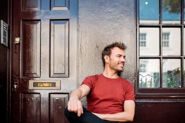 Человек сидит в скамейке на фоне красивых бордовых