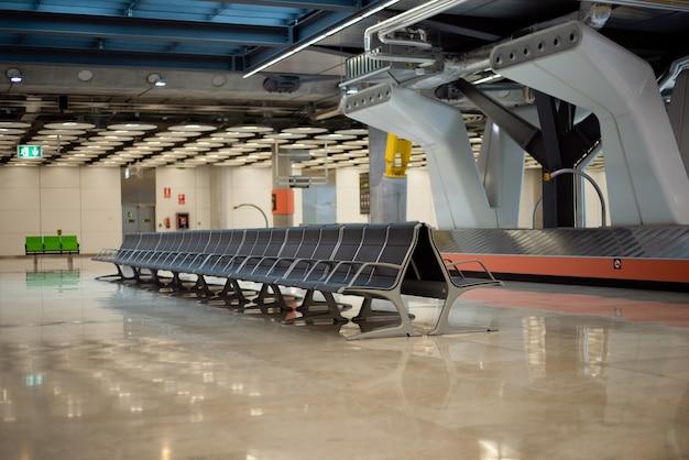 Пустой конвейер багажного отделения аэропорта и сидения