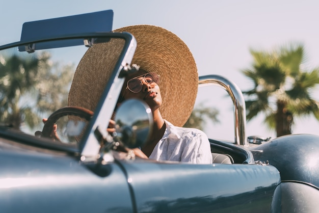 黒人女性がビンテージコンバーチブル車を運転