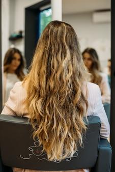 美容院に座っている長い髪の女