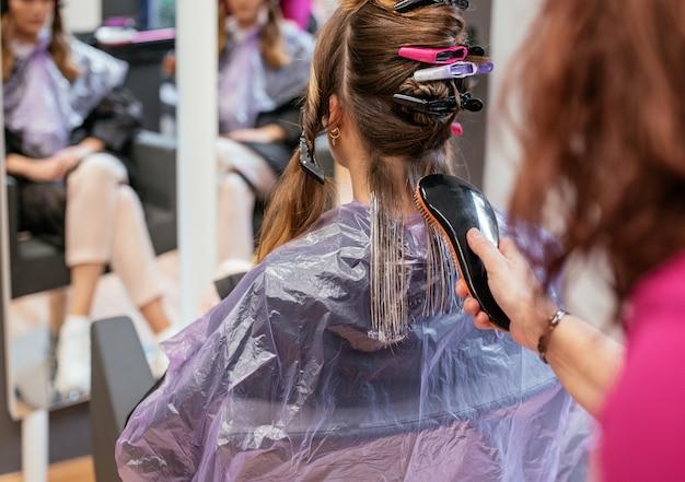 Парикмахер, окрашивающий волосы женщины
