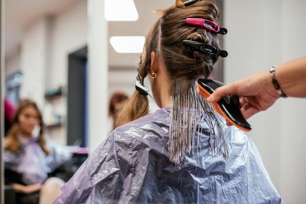女性の髪を染める美容師