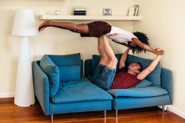 Обрадованная многонациональная пара, весело проводящая время вместе в гостиной