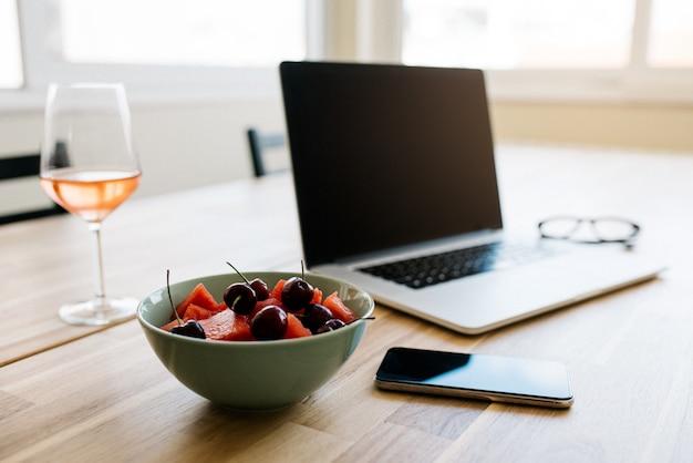 テーブルの上にデバイスと新鮮なベリーを備えた快適な作業スペース