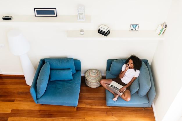 Счастливая молодая женщина с помощью устройств на дому