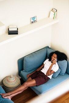 自宅で休んでいる間スマートフォンで呼び出す陽気なアフリカ系アメリカ人女性