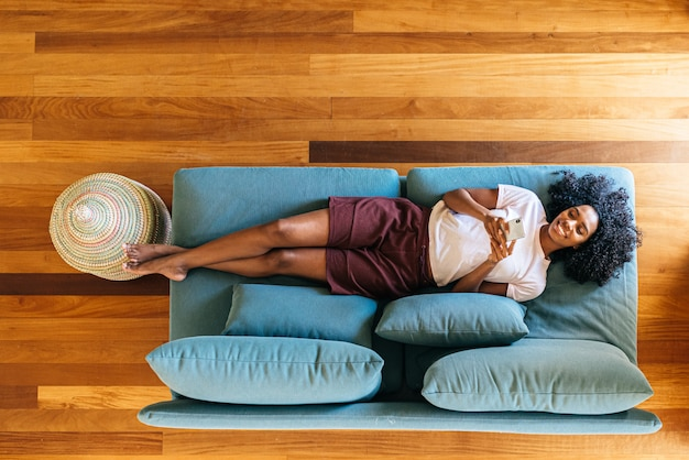Молодая женщина в чате на смартфоне, лежа на диване у себя дома