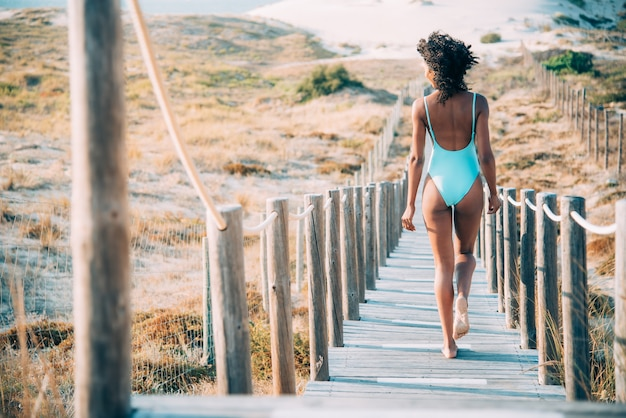 ビーチで木製の歩道橋を歩いて水着を持つ若い女性