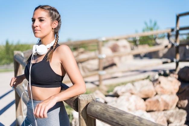 Закройте вверх по портрету женщины делая спорт отдыхая напольная усмехаясь и слушая музыка