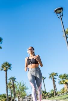 美しい若いスポーツ屋外音楽を聴く公園でジョギングを実行している女性