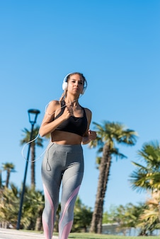 Красивая молодая спортивная женщина, бег трусцой в парке на открытом воздухе прослушивания музыки