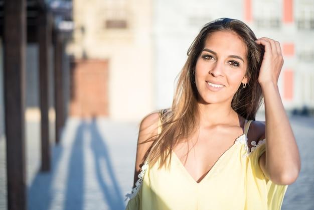 黄色のドレスと屋外をすぐに孤立した笑顔若いきれいな女性