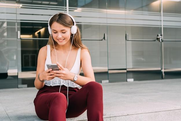 Молодая женщина, сидя на лестнице, слушая музыку на мобильном телефоне