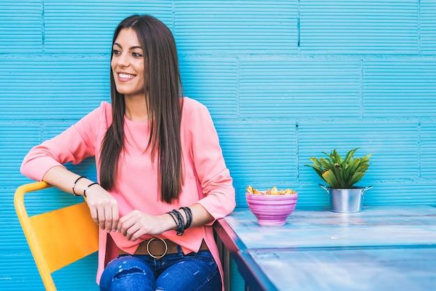Счастливая молодая женщина, сидения в ресторане