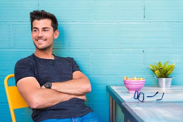 幸せな若い男がレストランの座席