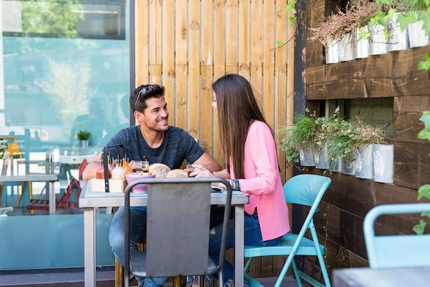 Счастливая молодая пара сидения на террасе ресторана, едят гамбургер