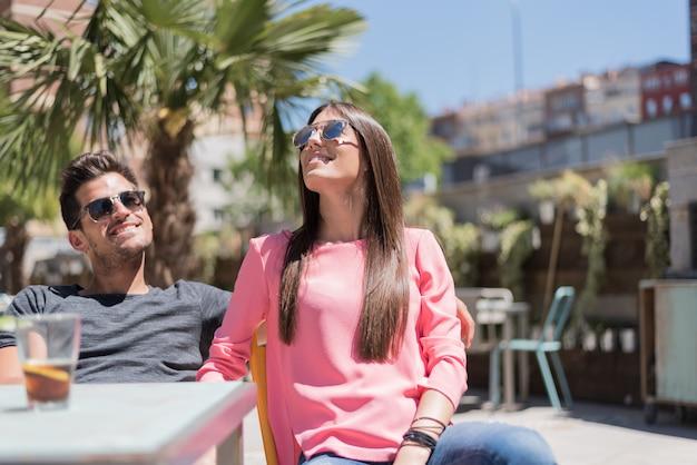 Счастливая молодая пара сидит на террасе ресторана