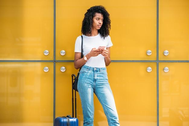 スーツケースの近くに立っている間携帯電話を使用して女性