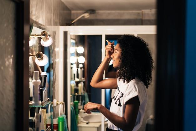 自宅で化粧をしている女性