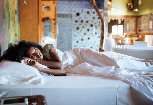 Красивая черная женщина спит в постели