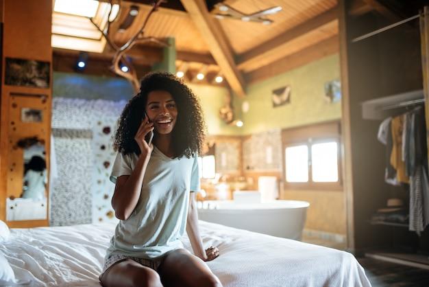 Женщина на кровати с мобильным телефоном