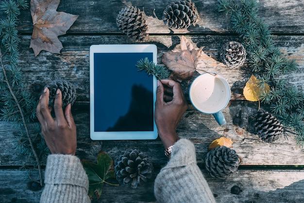 Руки женщины работая на таблетке в деревянном столе с кофе и соснами напольными