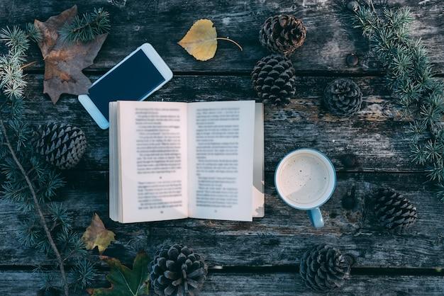 本とコーヒーと松の屋外の木製テーブルの上の携帯電話