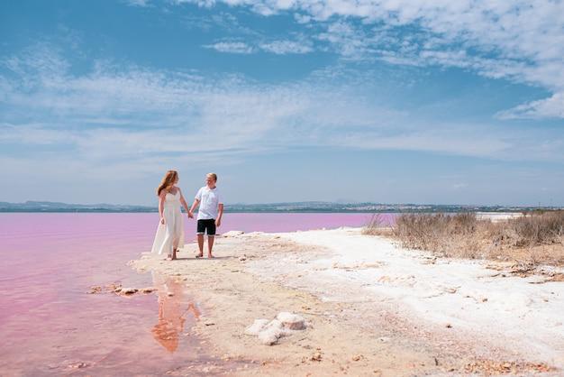 Милая пара подростков, прогуливаясь по берегу удивительного розового озера