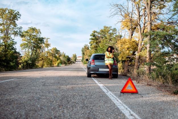 壊れた車と三角形の女性