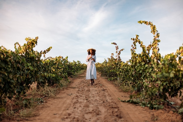 ブドウ畑の真ん中にある道を歩く若い女性