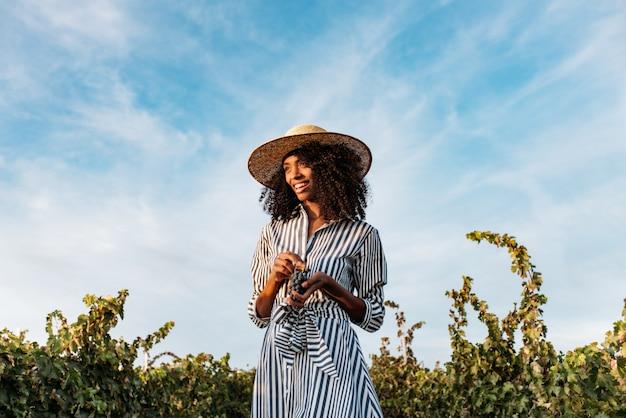 Молодая женщина, идущая в пути посреди виноградника