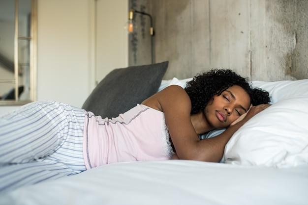 Красивая черная женщина, лежа на кровати спать