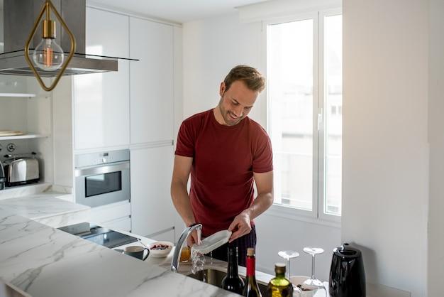モダンなキッチンでお皿を洗う人