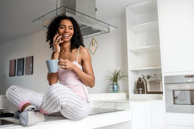 携帯電話でコーヒーを飲む女性