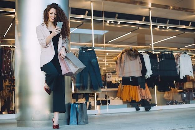 Счастливая красивая молодая рыжая женщина делает покупки и говорить по мобильному телефону