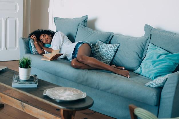 Красивая черная молодая женщина спит на диване
