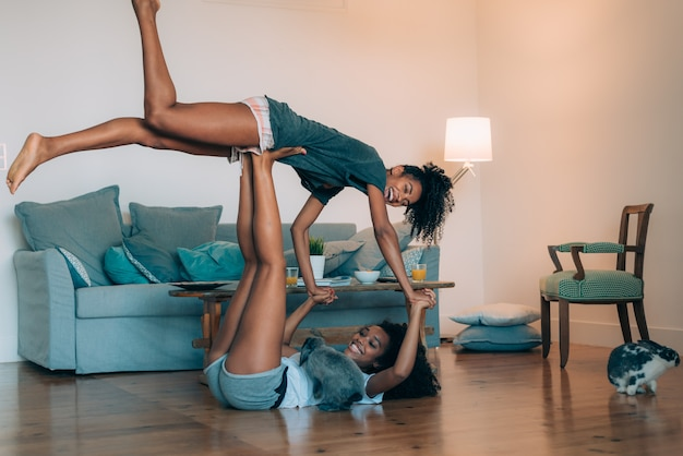 Счастливые молодые две негритянки отдыхали дома играя
